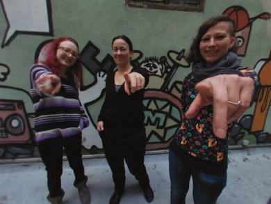 Drei junge Frauen zeigen in die Kamera.