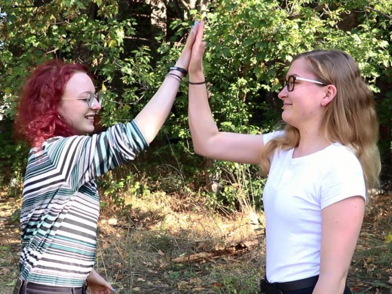 Zwei junge Frauen klatschen sich ab.