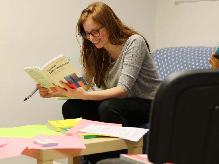 Eine junge Frau liest ein Buch.